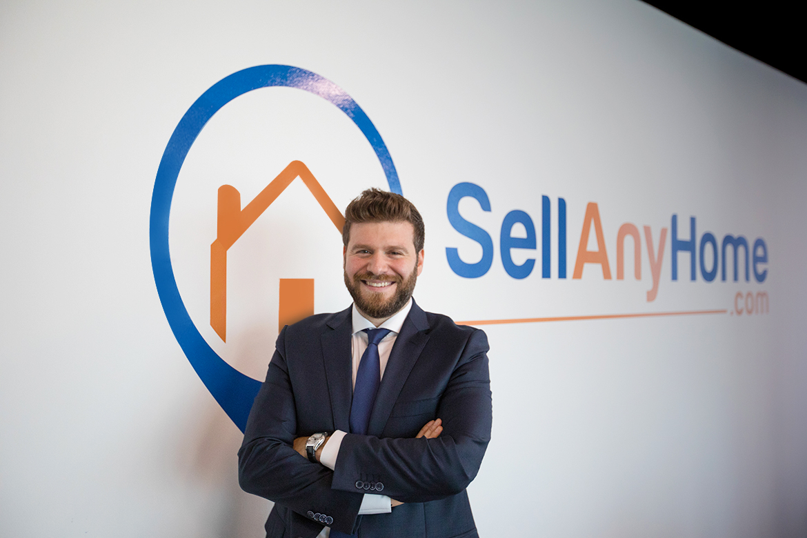 Omar Chihane wearing a suit with the company's logo behind him. Sellanyhome.com