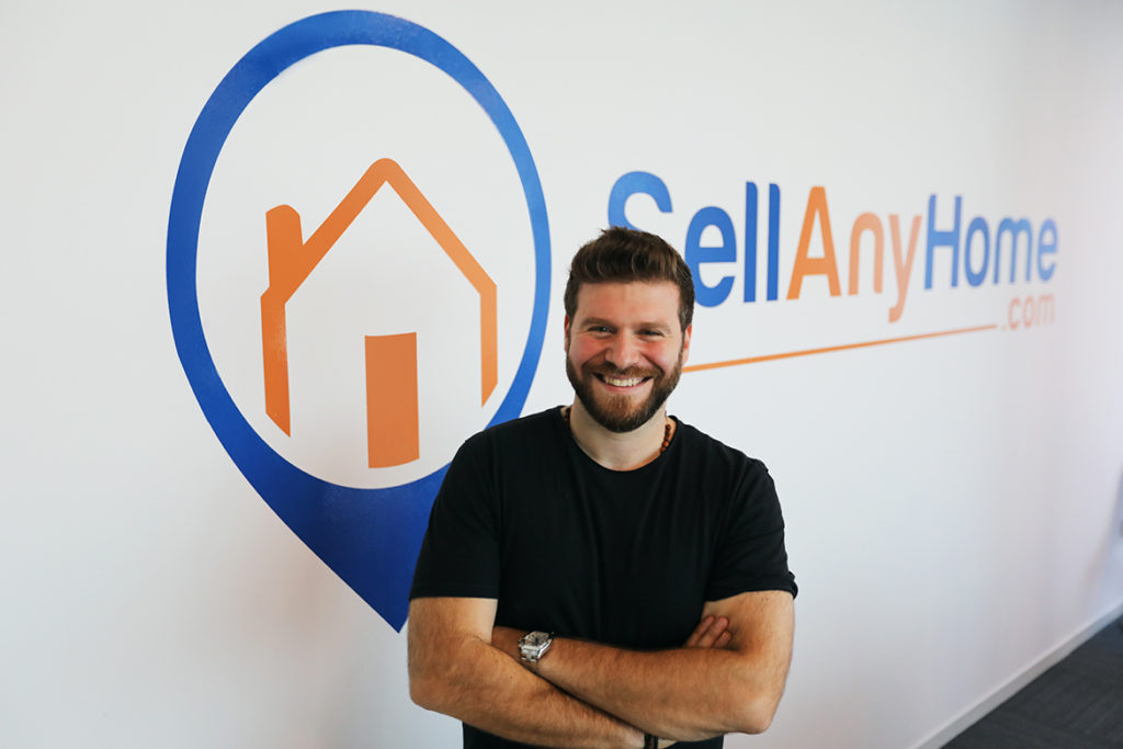 Omar Chihane wearing a black shirt with SellAnyHome on background